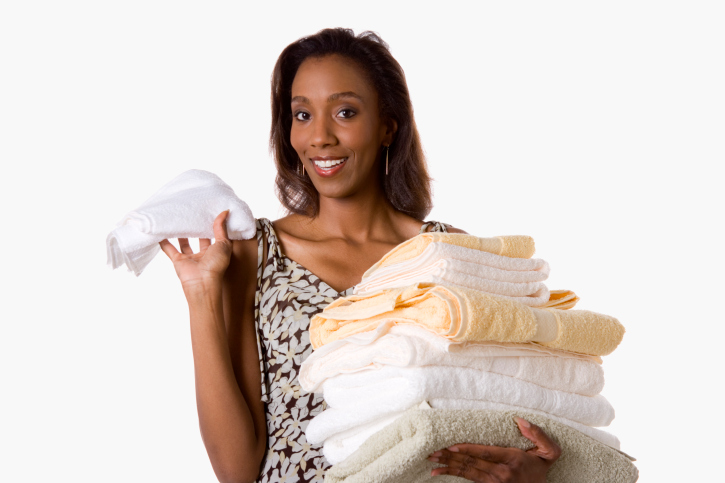 African American woman holding stack of towels