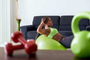 African American woman on exercise ball at home