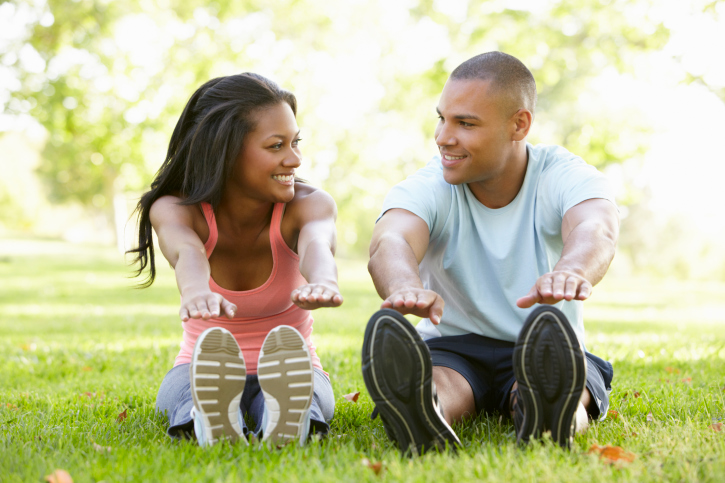 African American couple exercising outside in park