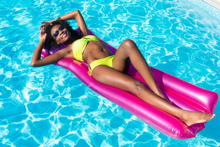 African american woman floating in pool