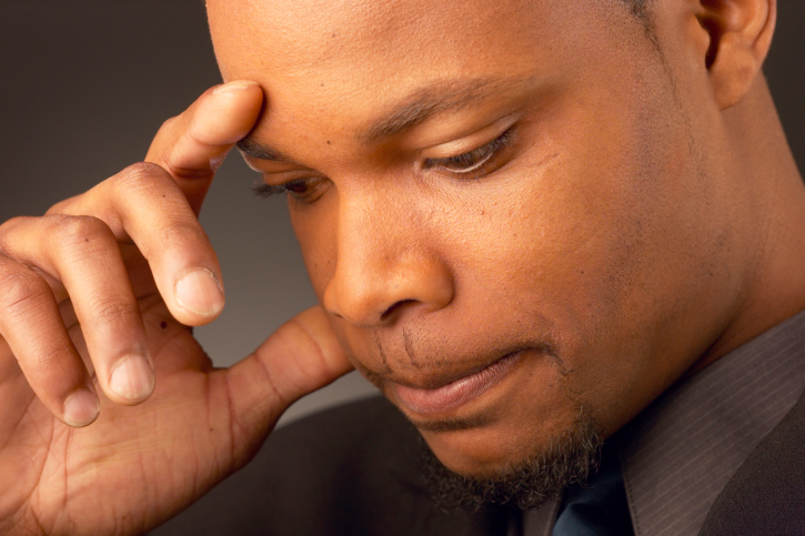 African American man looking down serious frustrated