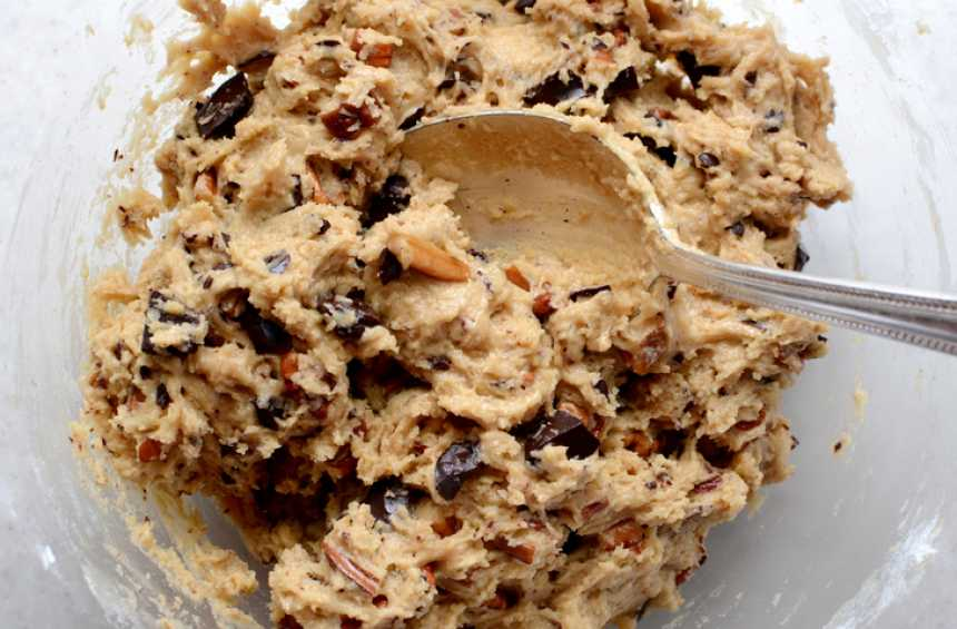 Raw cookie dough being mixed with chocolate chunks and chopped pecan nuts