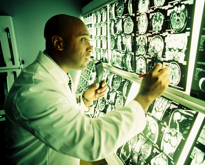 African American doctor looking at MRI scans