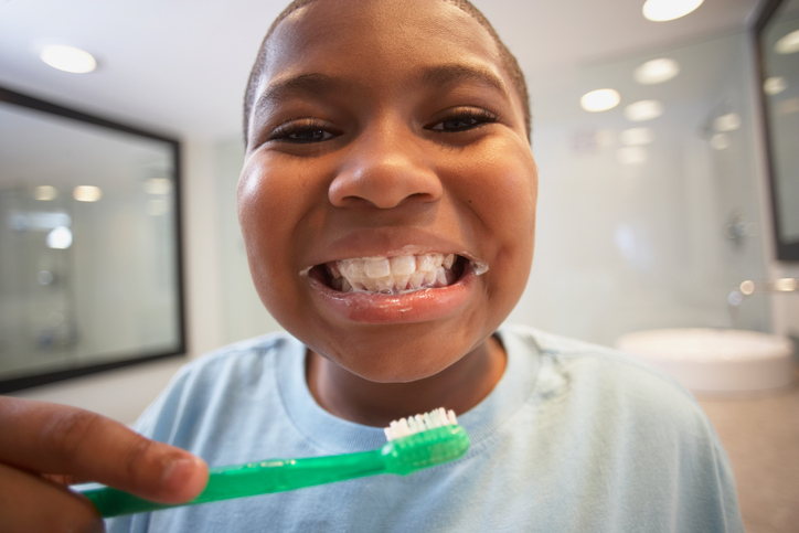African American boy brushing teeth