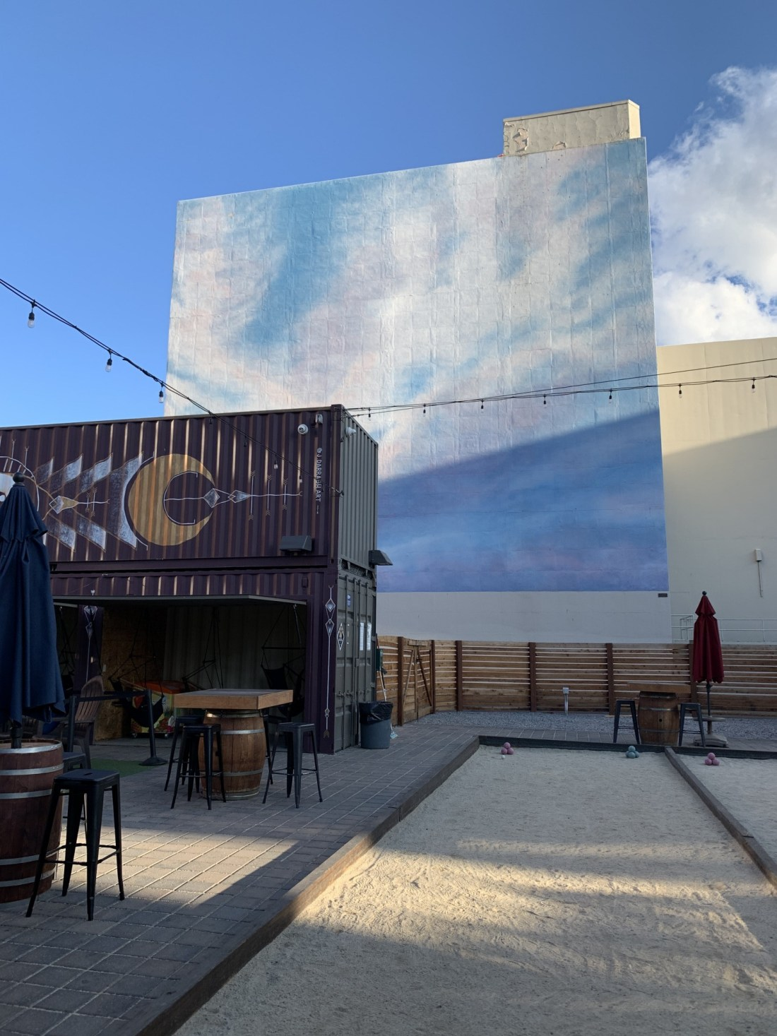 The Eddy Bar, sky mural and bar inside shipping container.