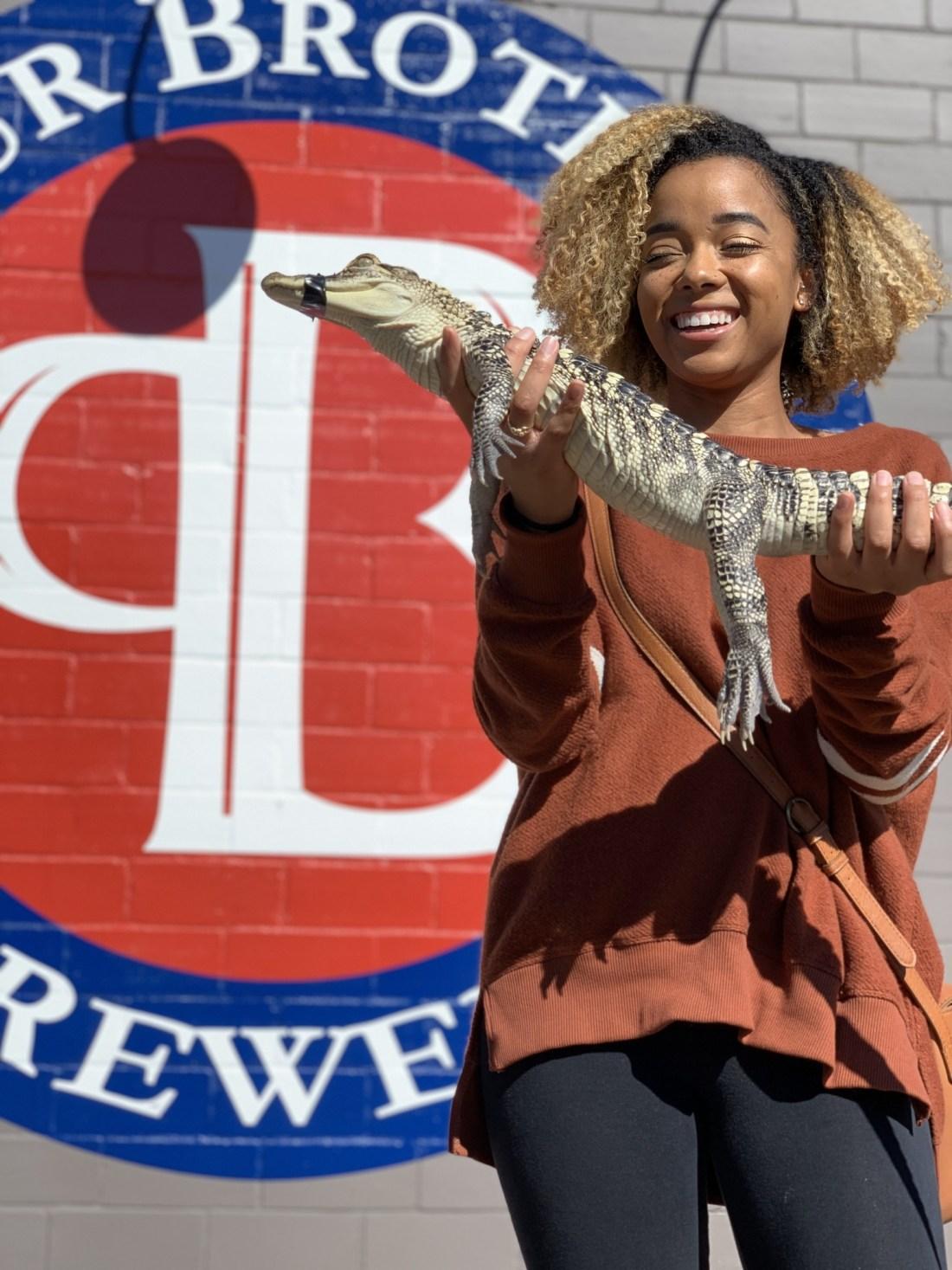 Woman holding alligator
