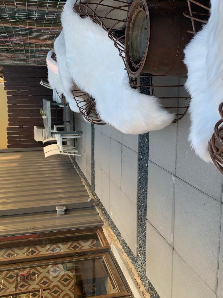 Side Patio with chairs covered in white fur blanket