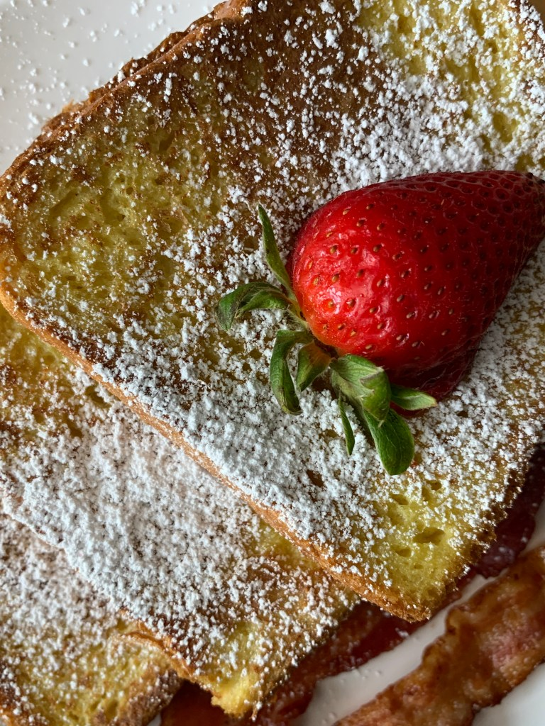 French Toast with Strawberry garnish and bacon