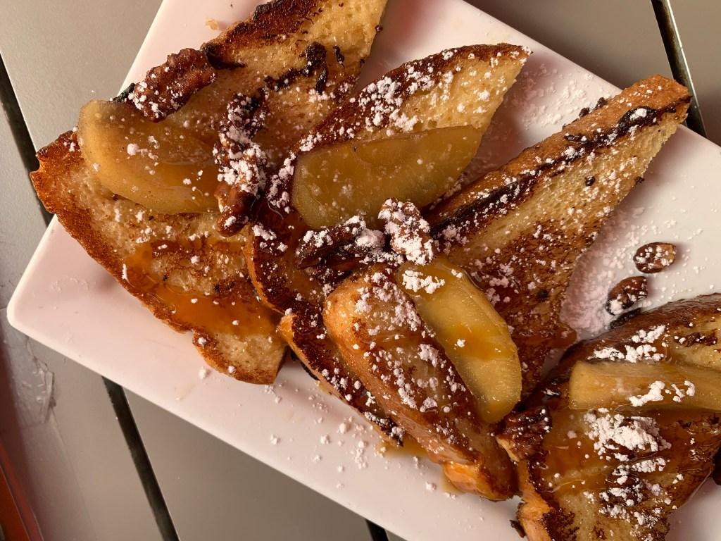 White plate with three pieces of french toast topped with fruit