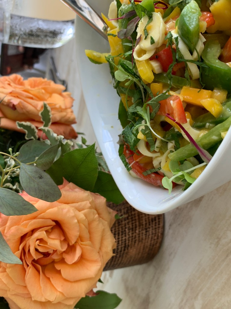 Flowers on a table with a white bowl of salad in the foreground