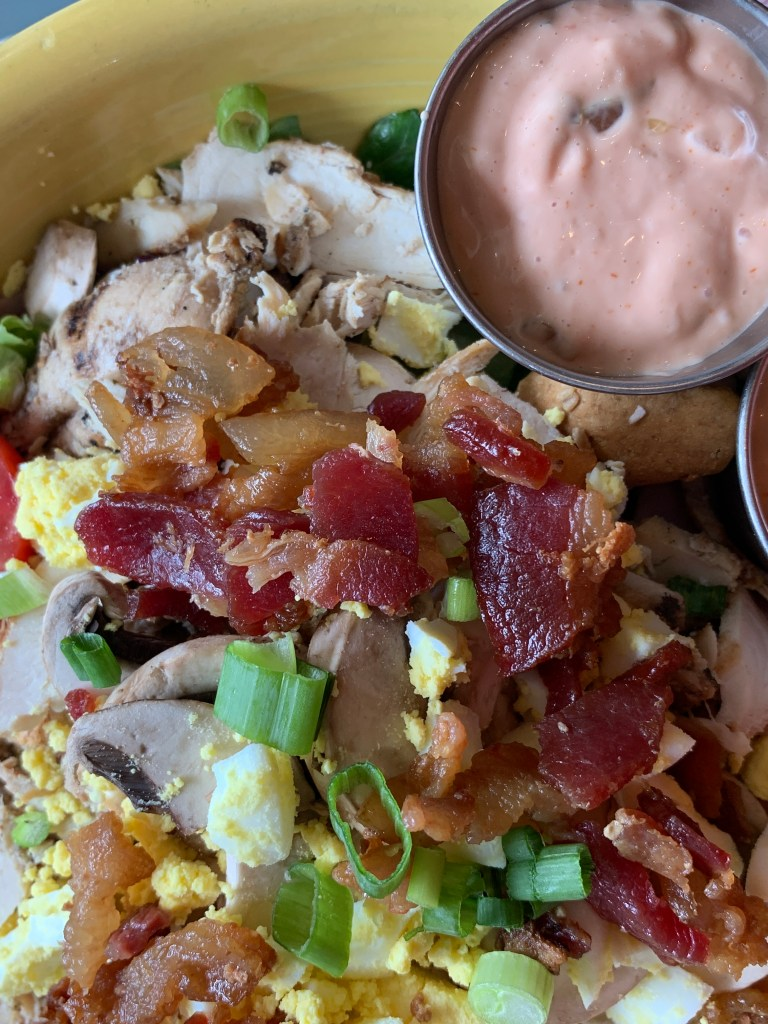 Salad topped with bacon, eggs, green onion and two small metal cups of dressing in a yellow bowl
