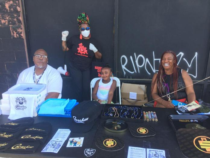 Hammer member posing with three artists selling goods