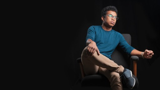 Feature. A picture of a Black masculine person sitting on a chair looking pensively.