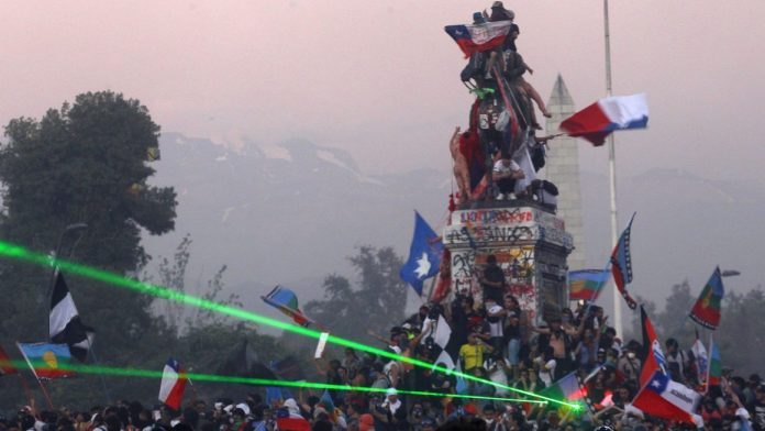 Chilean protesters climb statue, demanding freedom and justice.