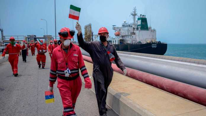 A worker of the Venezuelan state oil company PDVSA waves an Iranian flag as the Iranian-flagged oil tanker Fortune docks at the El Palito refinery in Puerto Cabello, in the northern state of Carabobo, Venezuela, on May 25, 2020. (Photo by AFP via Getty Images)
