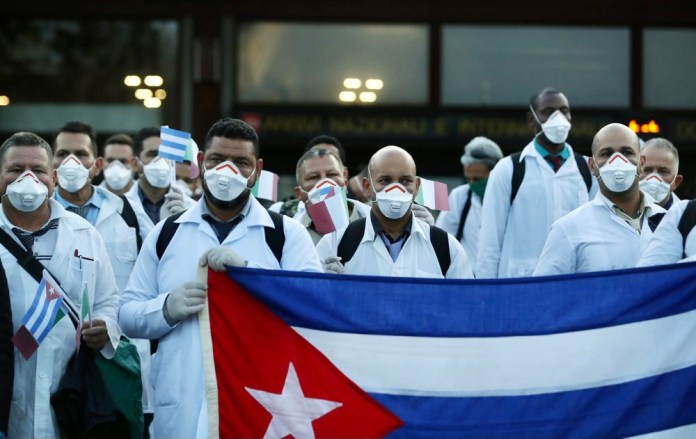 Cuban doctors hold their flag and pose for a photo