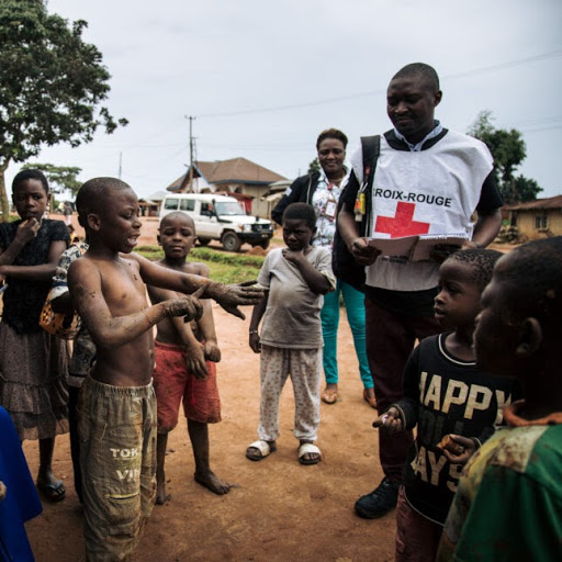 members of the International Federation of the Red Cross and the Congolese Red Cross going door-to-door speaking with families about the Ebola virus. ALEXIS HUGUET/AFP VIA GETTY IMAGES