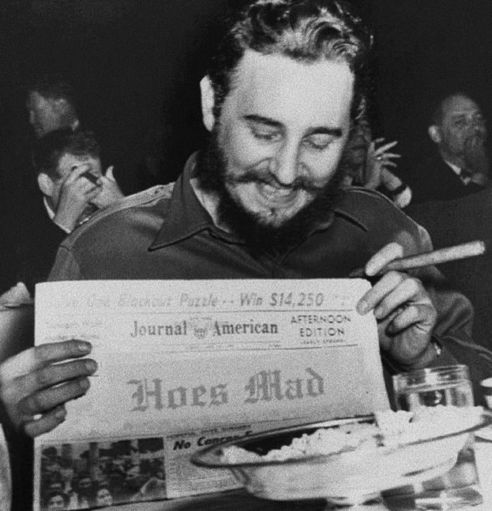 """Fidel holding up a photo saying """"Hoes Mad"""""""