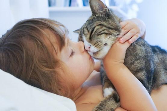 girl kissing cat
