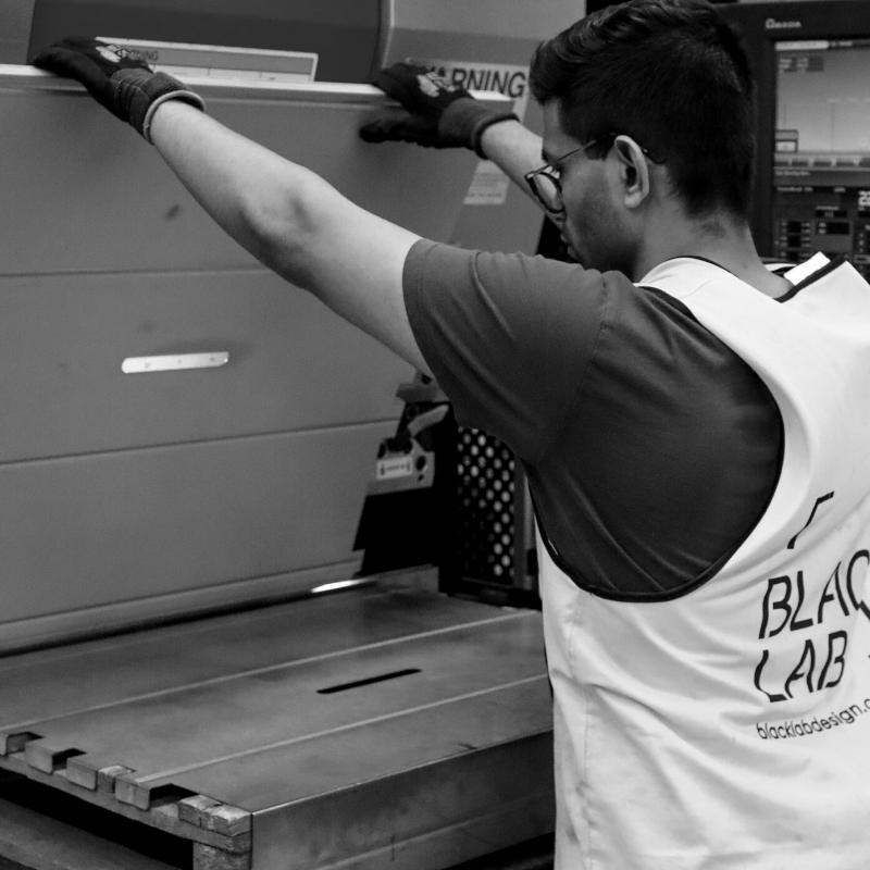 black and white image of man bending metal