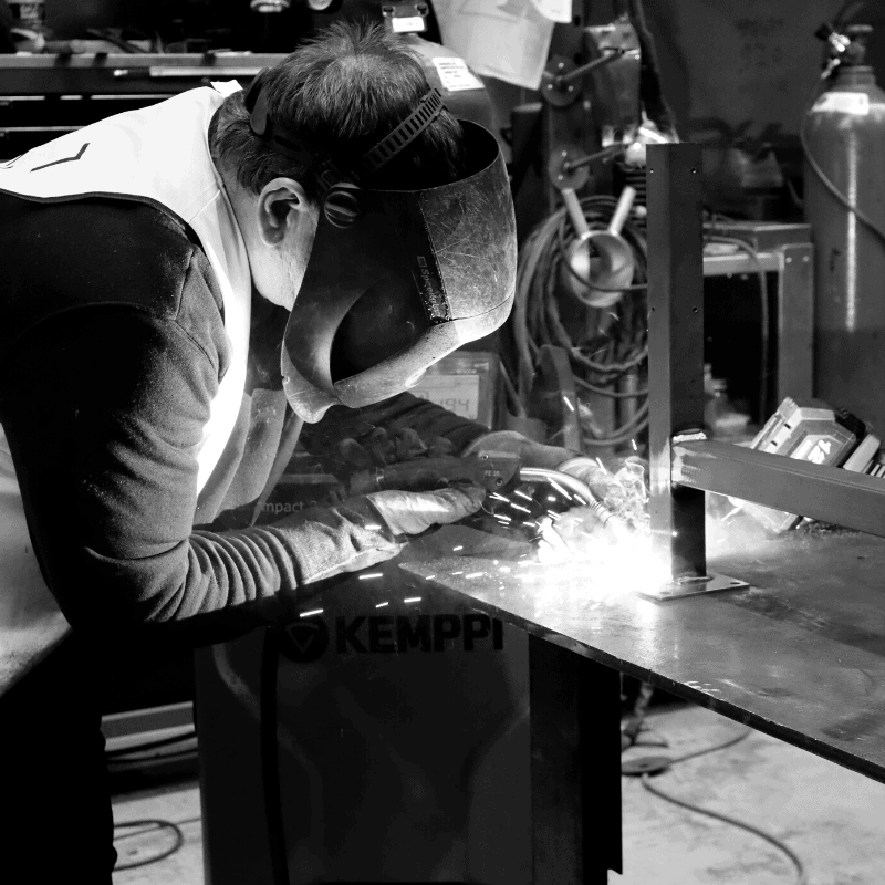black and white image of man welding