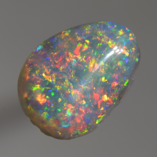 This floral pattern Dark Opal has brillant flashing red, green, and blue colours and would look very nice set in a ring.