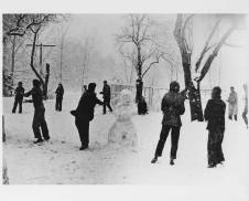 """Snowball fight, Lake Eden campus, Black Mountain College, ca. early 1940s. On back of the photograph: """"Jane Slater, standing to right of snow man."""" Photographer is identified as John Campbell. Courtesy of Western Regional Archives."""