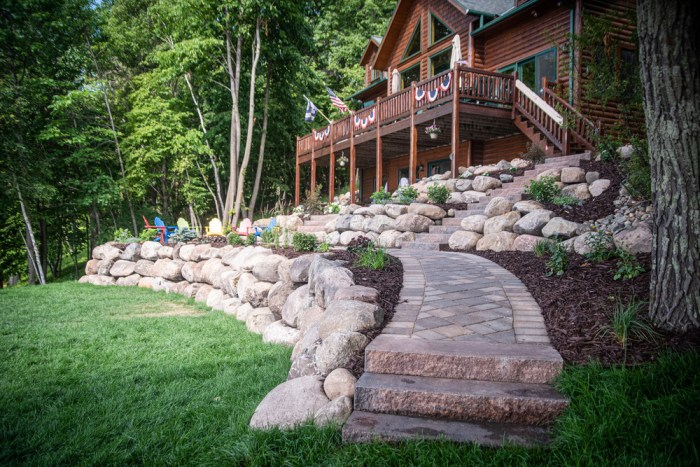 Stairs leading to paver walkway with boulder walls surrounding