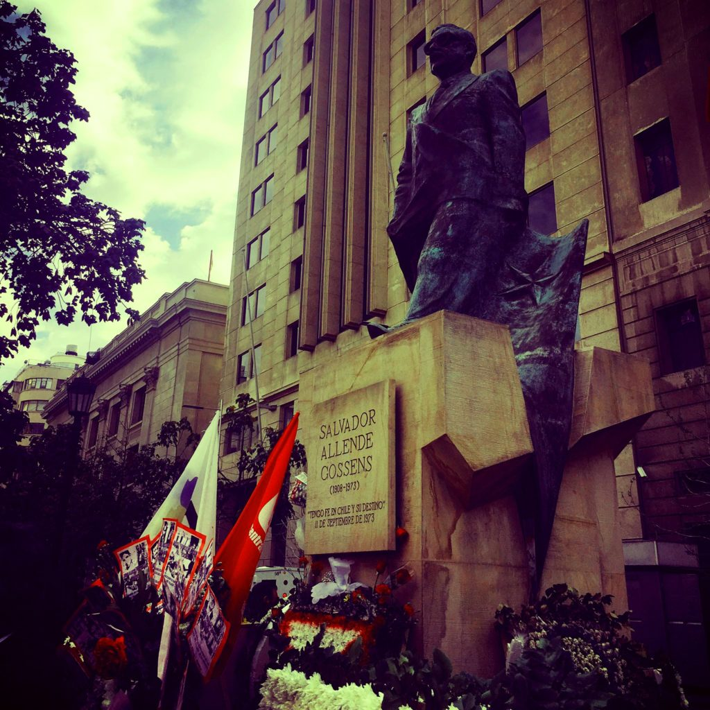Photo of Allende Memorial statue with wreaths and flags surrounding the base.