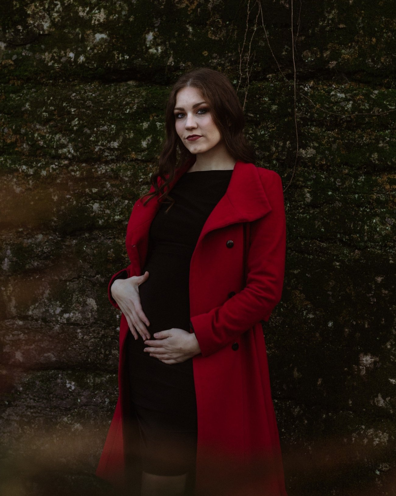 Girl in black dress and red coat holds pregnant belly