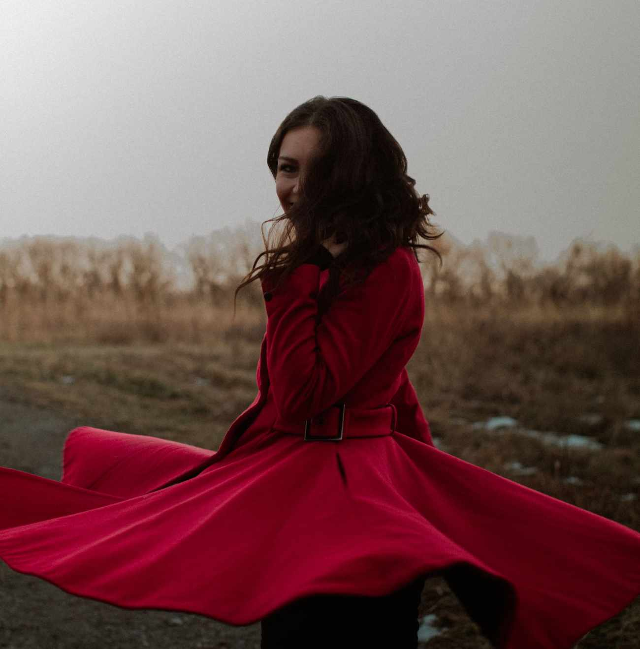 Woman spins dramatically in red coat