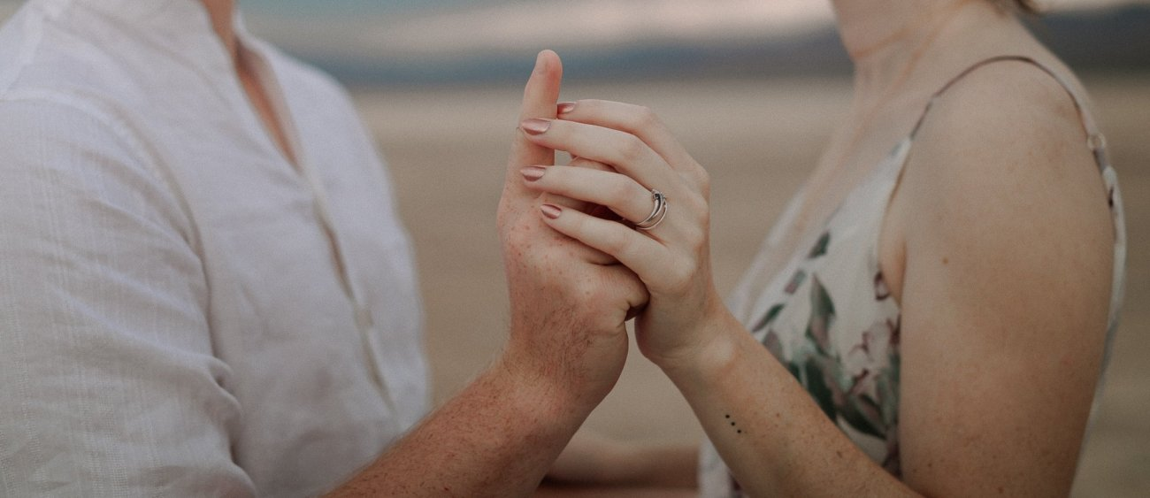 Close up of bride and groom holding hands at sunrise