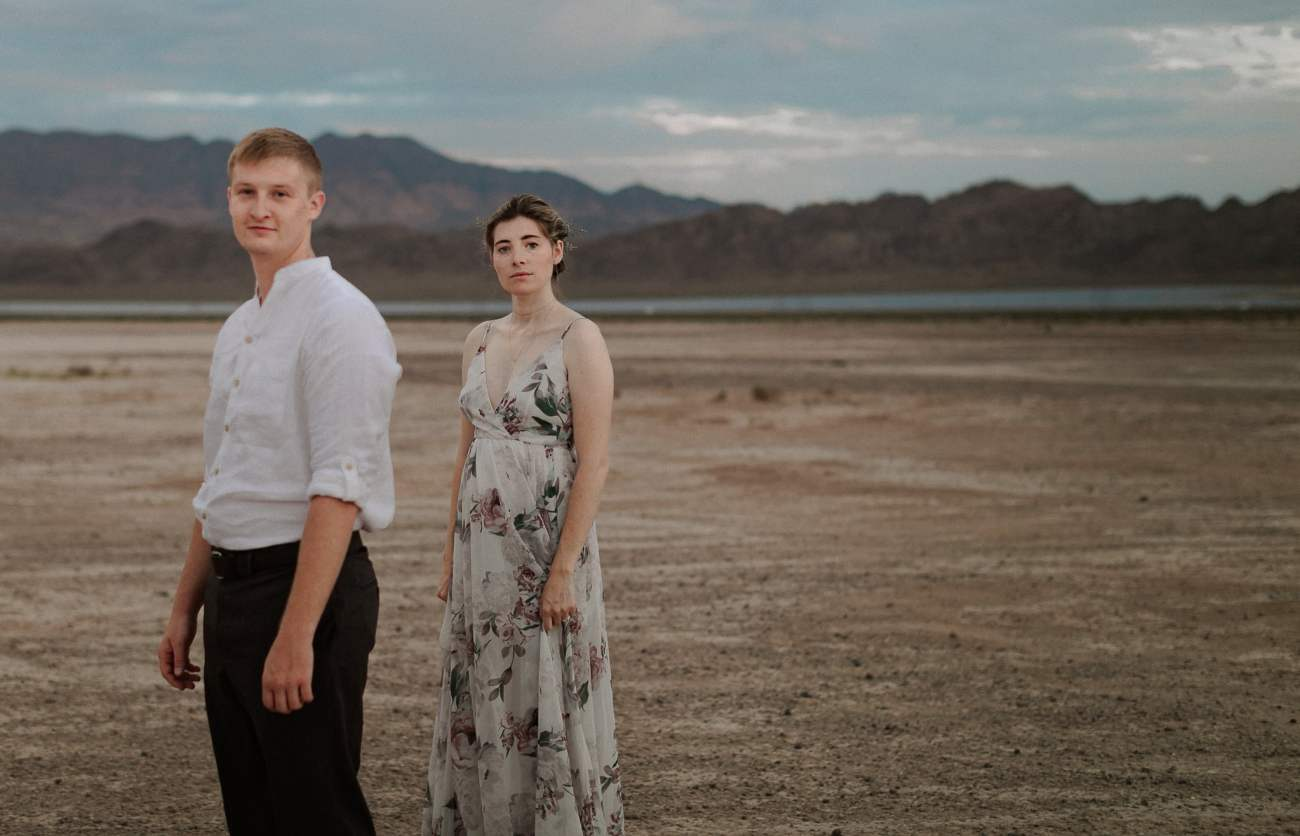 Groom looks at camera and bride stands behind him at dry lake bed