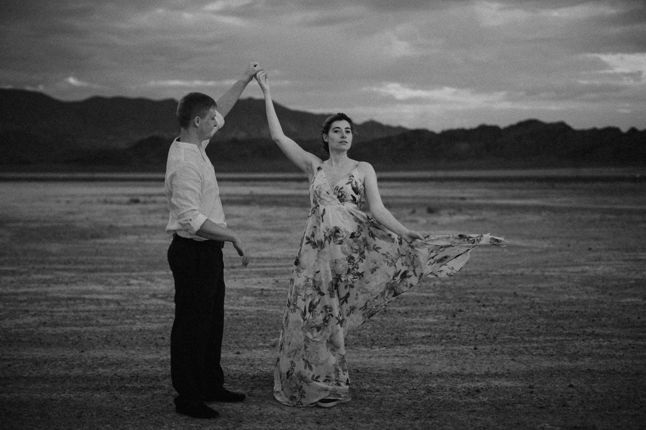 Groom spins bride with flowy floral dress