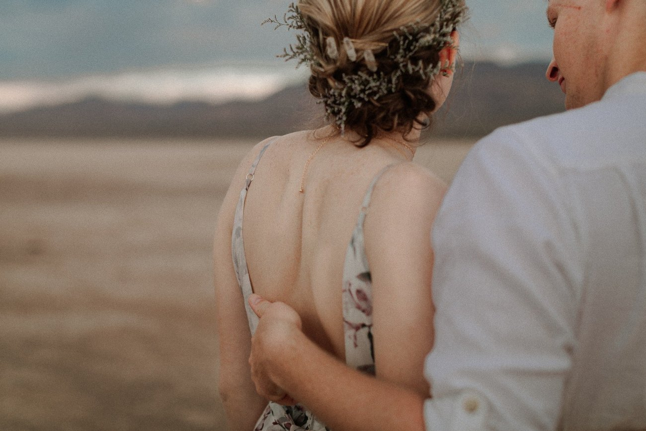 Groom caresses bride back at Las Vegas Dry Lake Bed at sunrise