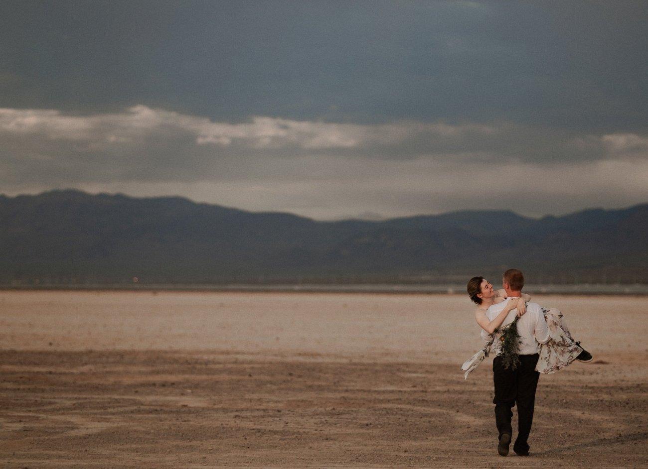 Groom carries bride at Las Vegas Dry Lake Bed at sunrise