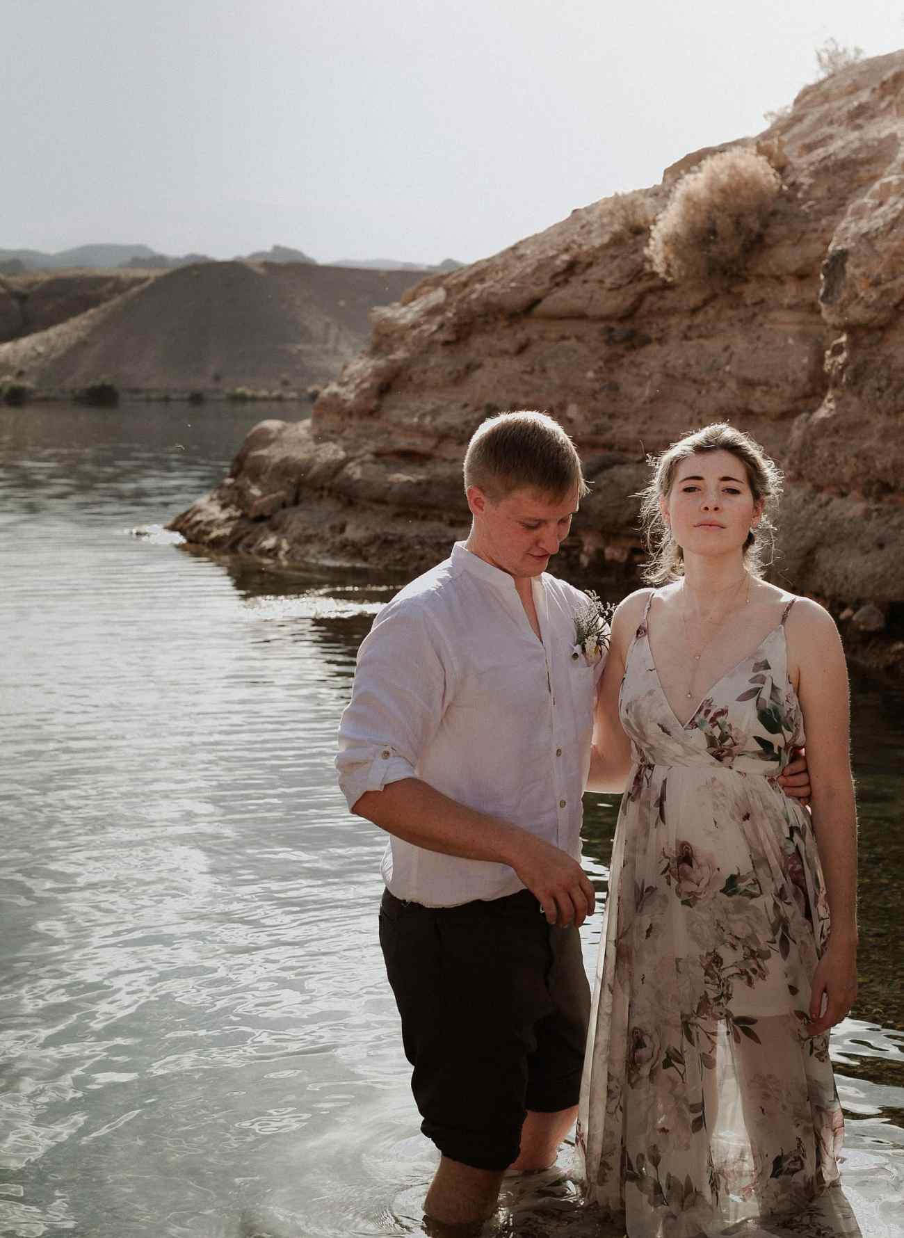 Bride and groom stand in Colorado River at Sunrise