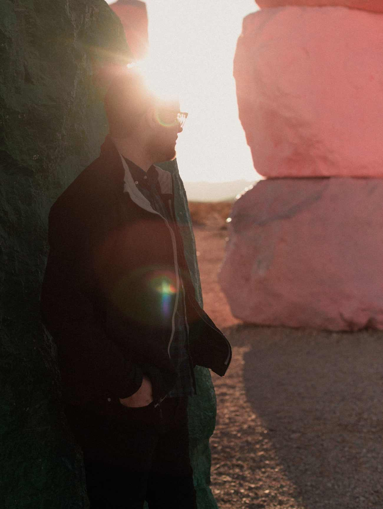 Man looks into sunset at Seven Magic Mountains