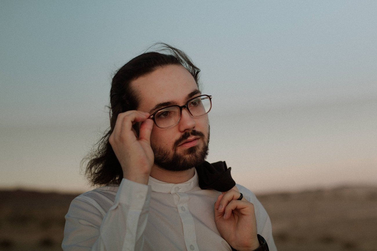 Groom adjusts glasses for las vegas desert elopement