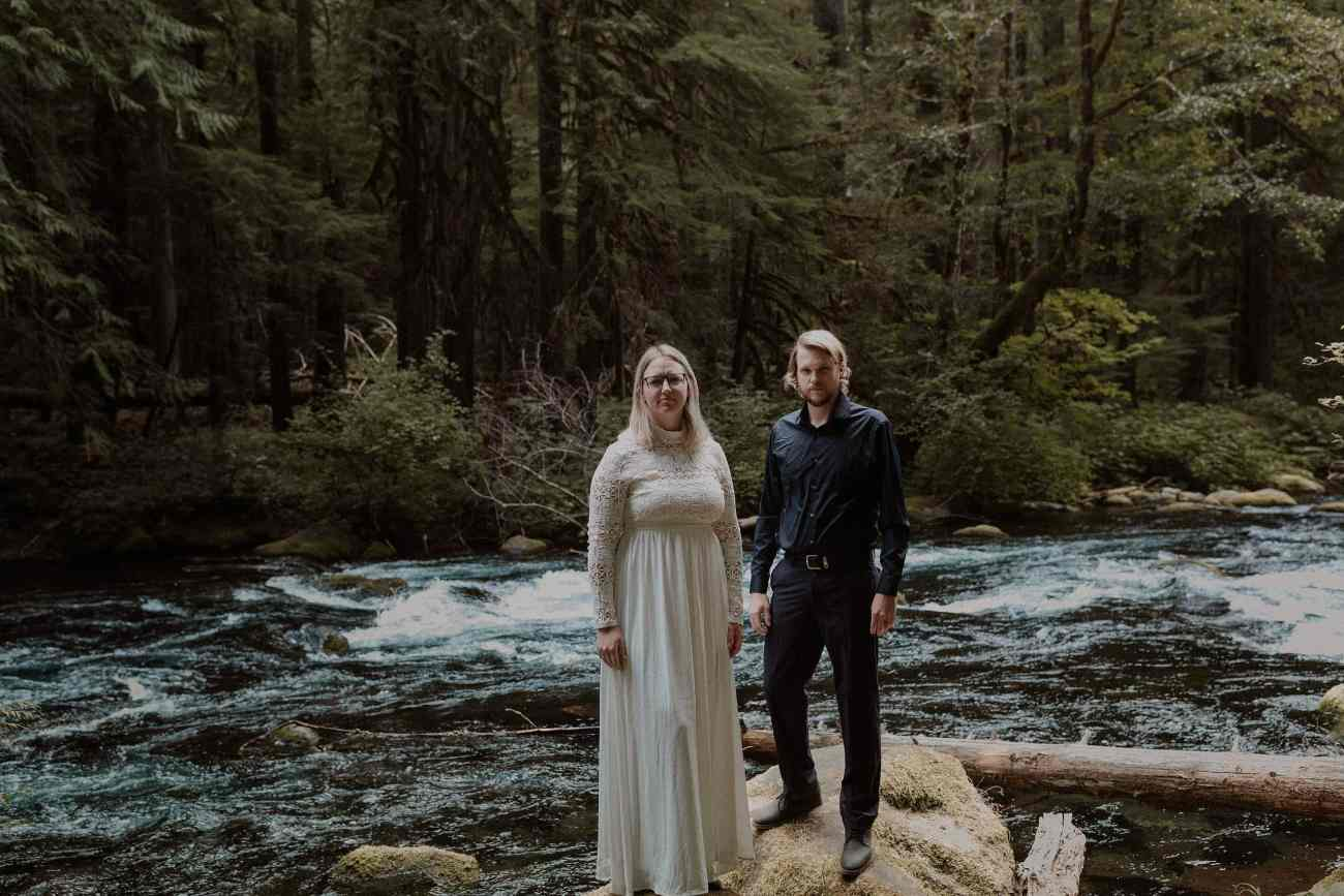 Elopement couple standing on rocks by Mackenzie River in Oregon