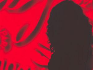Ombra di Flavia dietro sfondo rosso con scritte Campari