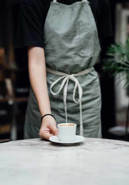 crop waitress serving cup of coffee