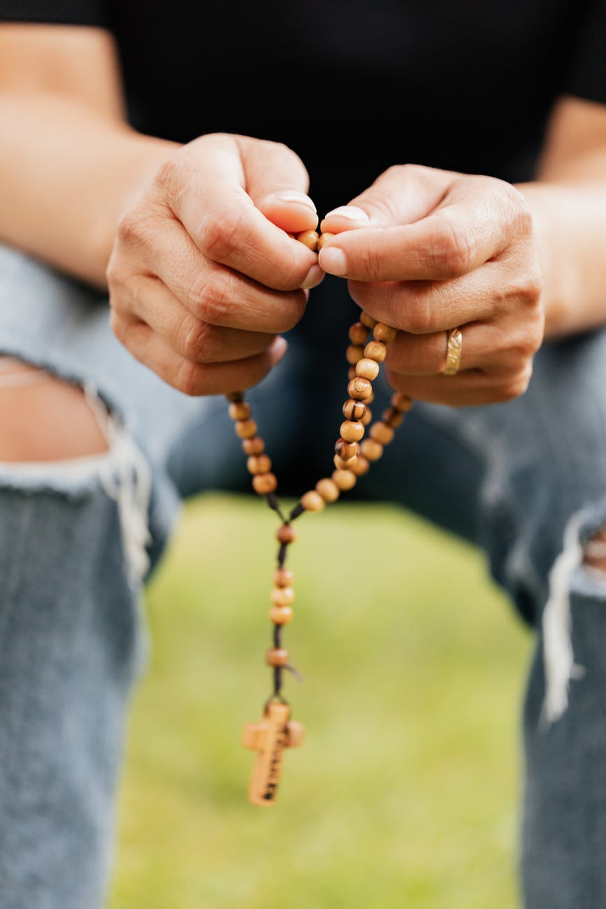 person holding brown beaded necklace