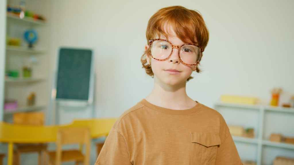 shallow focus photo of a boy in brown crew neck shirt wearing eyeglasses