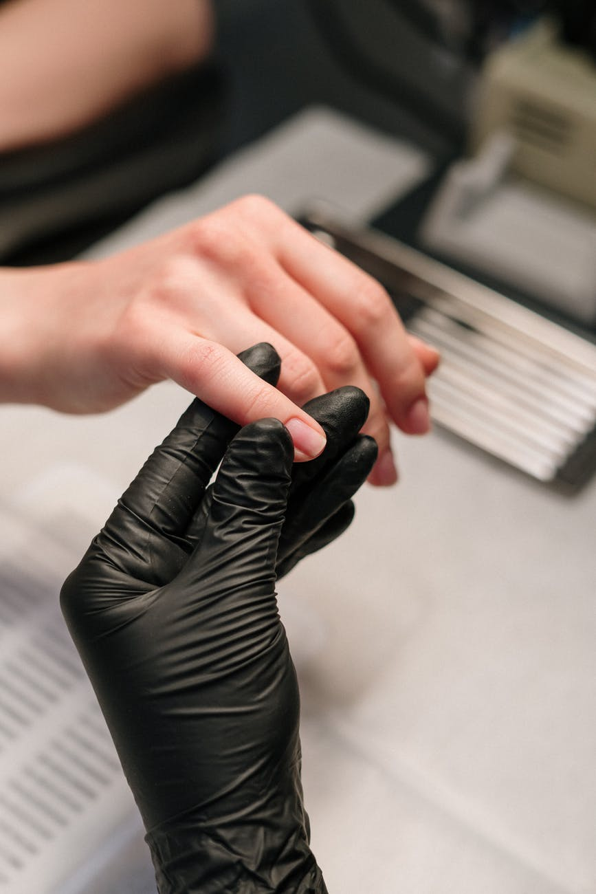 person in black leather gloves holding black and white book