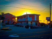 New Art Release Titled; Small Motel On The Beach At Sunrise. Digital Art of the Sierra Suites, at the city limit of Daytona Beach, North of Daytona Beach Shores, at sunrise two coral and white two story buildings with the sun rising behind them over the
