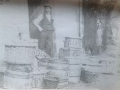 c1910 Boathouse. Worker stands at door with fruit baskets (PV)