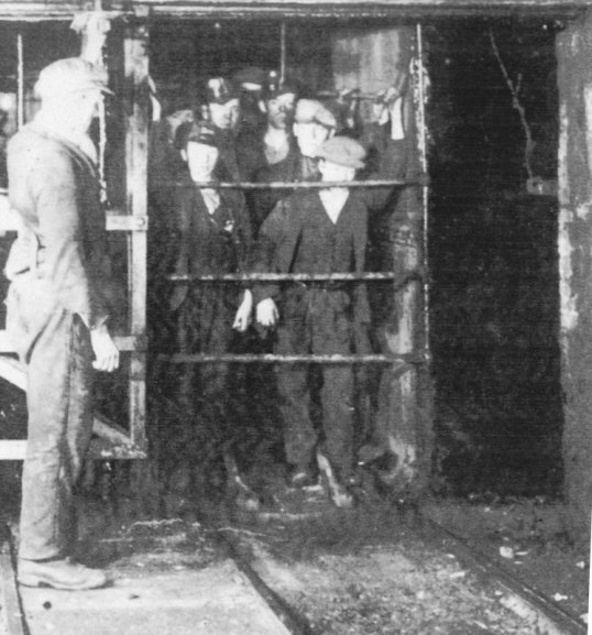 WL._403__Miners_in_a_cage_at_the_Pit_Bottom_showing_cage__shaft_and_pit_bottom_man._c.1920