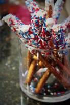 White chocolate-dipped pretzel sticks rolled in patriotic sprinkles