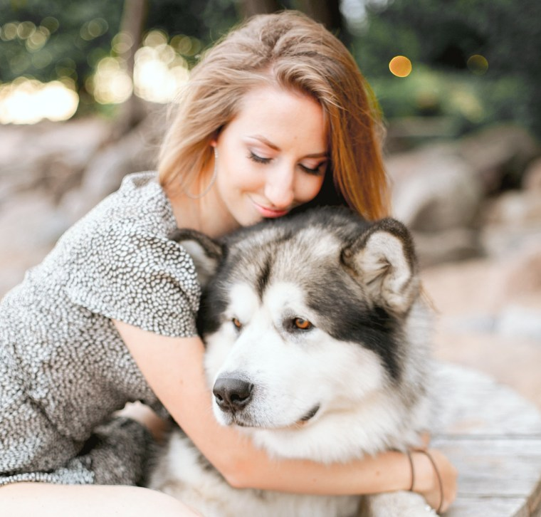 woman-in-gray-sweater-hugging-black-and-white-siberian-husky-3662756